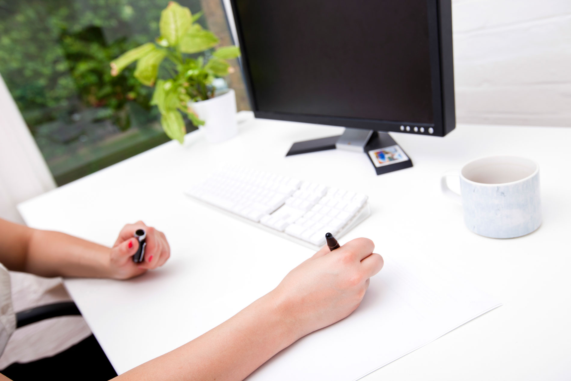 Cropped image of businesswoman noting on paper at computer desk